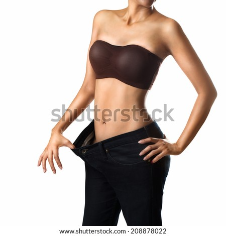 Woman shows her weight loss by wearing an old jeans, Isolated Over white - stock photo