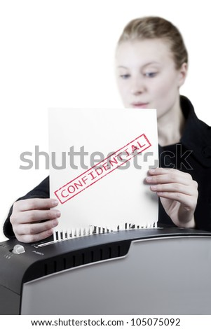 woman shredding a confidential paper - stock photo