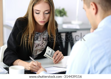 Woman signing documents after receiving a batch of hundred dollar bills. Venality, bribe, corruption concept - stock photo