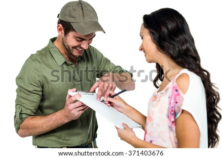 Woman signing for pack delivery with smiling postman on white screen - stock photo