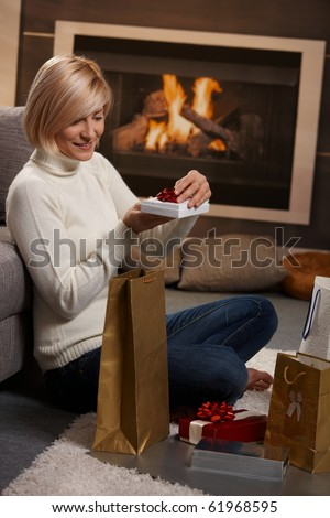 Woman siiting on floor at home in front of fireplace wrapping presents for Chrismas.