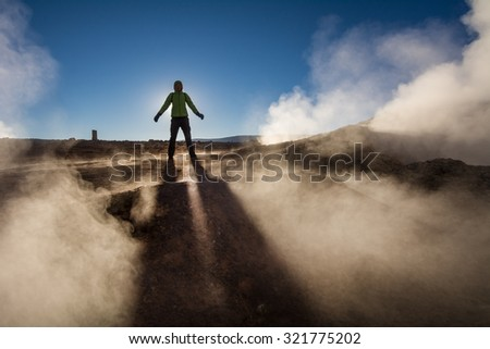 Woman silhouette against sunrise, Sol de Manana geysers, Salar de Uyuni tour, Andes, Bolivia - stock photo
