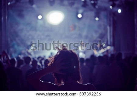 woman silhouette in a crowd at a concert in a vintage light, noise added - stock photo