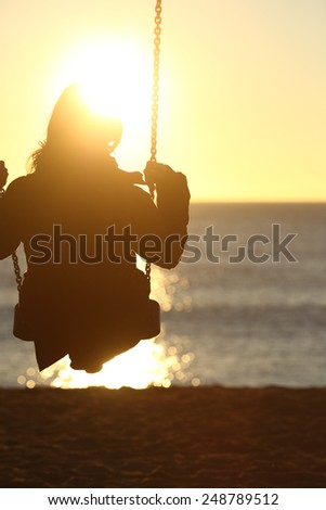 Woman silhouette swinging at sunset on the beach and watching the sun - stock photo