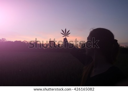 Woman silhouette with cannabis - stock photo