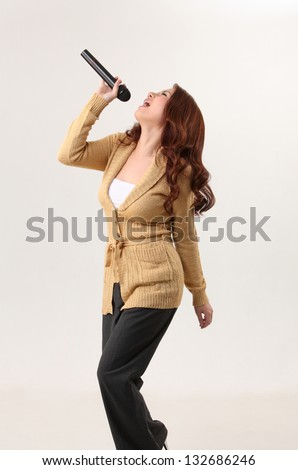 Woman singing, holding wireless microphone - stock photo