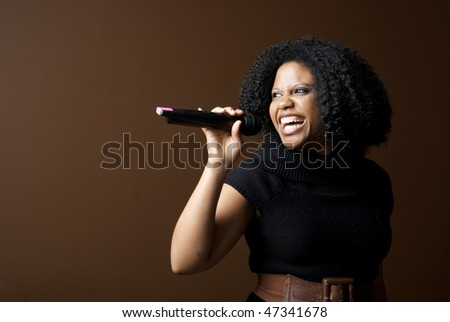 Woman singing into microphone with copyspace - stock photo