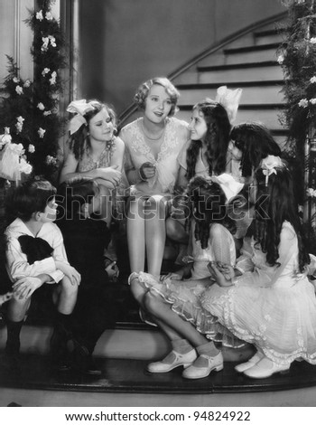 Woman singing with children on staircase at Christmas - stock photo
