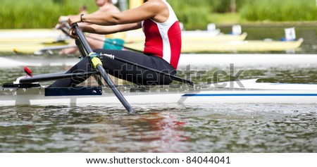 Woman Single sculls rower during the start of a rowing regatta - stock photo