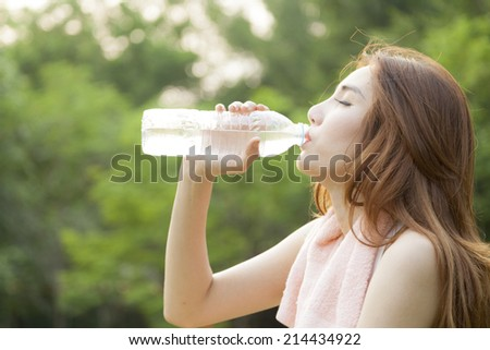 Woman sit and drink after exercise. On the lawn after a workout in the park.