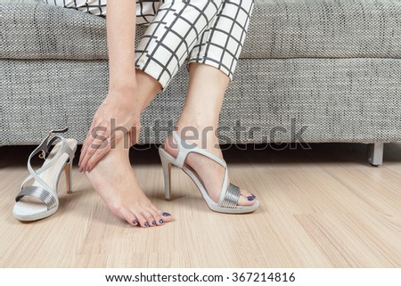 woman sit on chair and female hand with foot pain after, take shoes off - stock photo