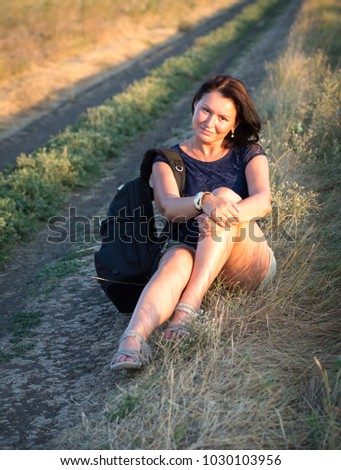 Woman sit with backpack hitchhiking along a road in countryside