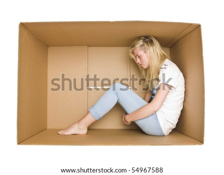 Woman siting in a cardboard box isolated on white background - stock photo