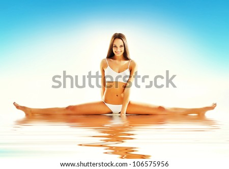 woman siting on straddle split in water - stock photo