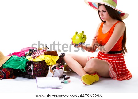 Woman sits near overfilled suitcase. Lady holds green money box. Money means a lot. Tired of travelling alone - stock photo