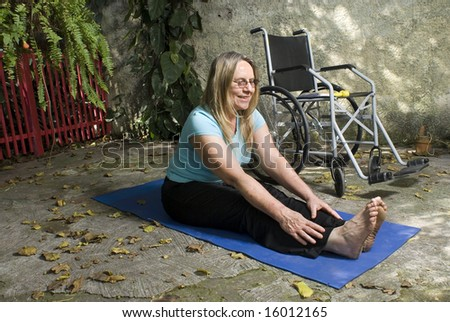 Woman sits next to a wheelchair on blue yoga mat outdoors. Her legs are extended and she  is stretching toward her feet. Horizontally framed photo. - stock photo
