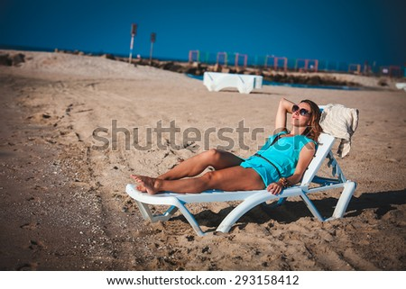 Woman sits on chair in sea sand sun - stock photo