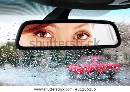 woman sits on driver's seat and Looks in the rear-view mirror - stock photo