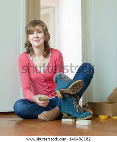 Woman sits on floor and cleans footwear