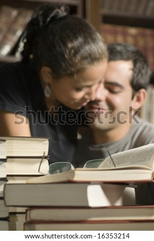 Woman sits on man's lap. There are books on the table and in the background. Vertically framed photo. - stock photo