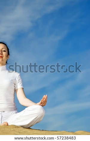 woman sits quietly in the lotus position on sand - stock photo