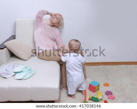 woman sits with her child, postpartum depression - stock photo