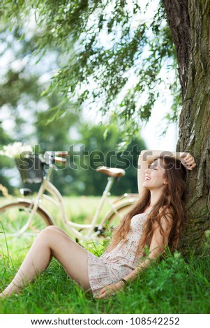 Woman sitting against tree - stock photo