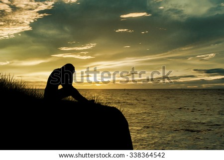 Woman sitting alone and sad depressed with meadow, Silhouette sunset. - stock photo