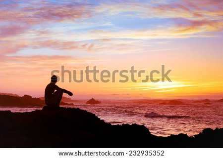 woman sitting alone at sunset near the sea, relaxing and thinking about the meaning of life - stock photo