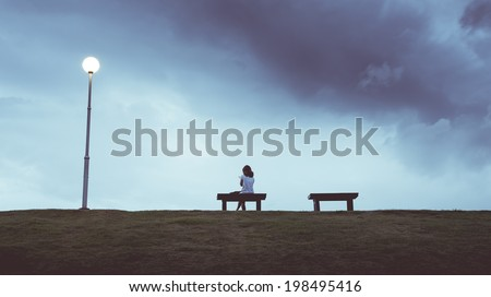 Woman sitting alone in a bench , vintage color - stock photo