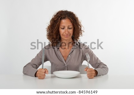 Woman sitting and waiting in front of an empty dish. Diet concept. You can place the food you prefer in the plate.