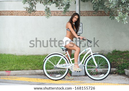 Woman sitting astride an old style bicycle. - stock photo