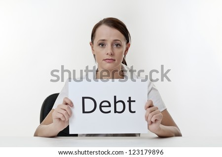 woman sitting at a desk worried about debt problems - stock photo