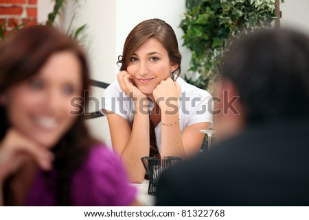 Woman sitting at a restaurant table with other diners in the foreground