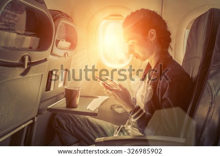 Woman sitting at airplane and looking to mobil phone. - stock photo