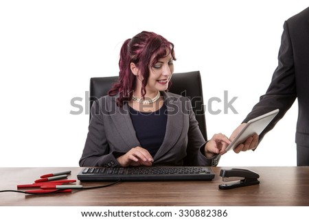 woman sitting at desk being showen something on a table by a male colleague at work - stock photo