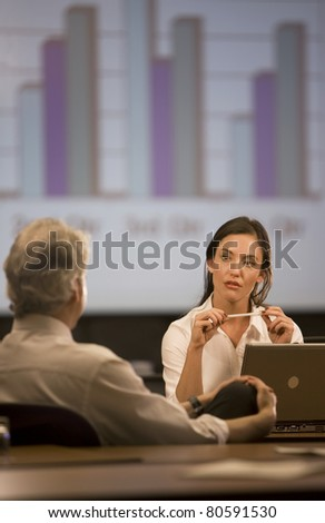 Woman sitting at desk talking to a man in the office. - stock photo