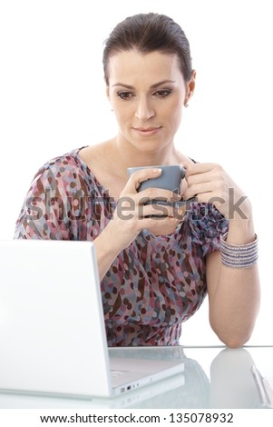 Woman sitting at desk with coffee mug handheld, looking at laptop computer screen, smiling.