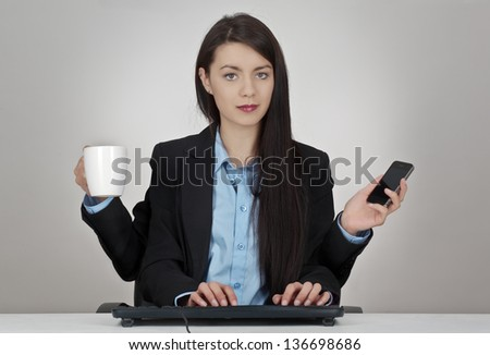 woman sitting at her desk with four arms two hands typing onto a keyboard and one holding a mobile phone and the other a cup of coffee or tea - stock photo