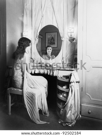 Woman sitting at her vanity table smiling into the mirror - stock photo