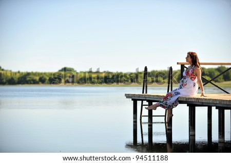 woman sitting  at   jetty. summer's day on lakeside