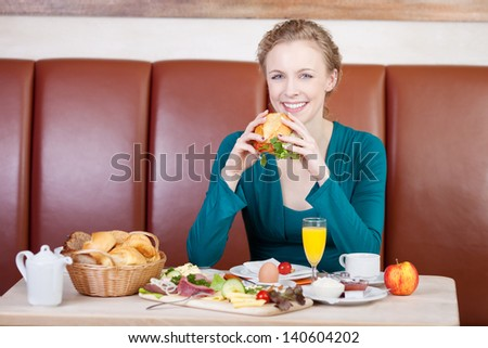 woman sitting at table and having breakfast in bakery - stock photo