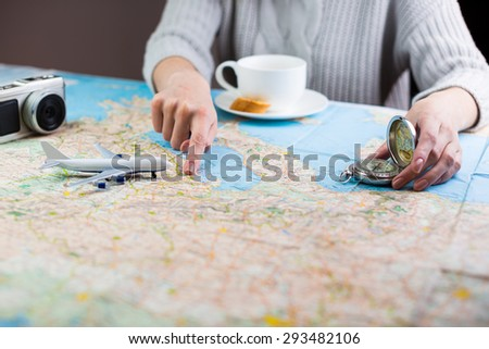 Woman sitting at table with map with paper airplane, compass, camera and visualises desire to travel. Holidays and tourism concept.  Shallow depth of field - stock photo