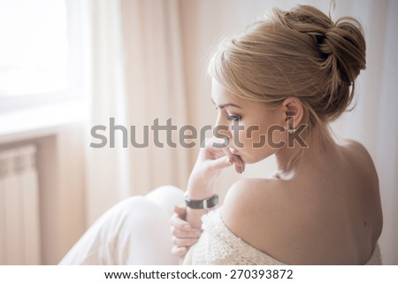 Woman sitting by the window - stock photo