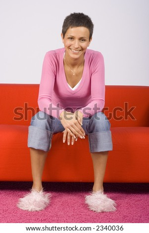 woman sitting comfortable on the red sofa, looks happy - stock photo