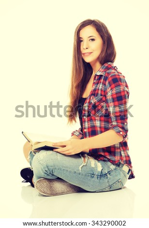 Woman sitting cross-legged and reading - stock photo