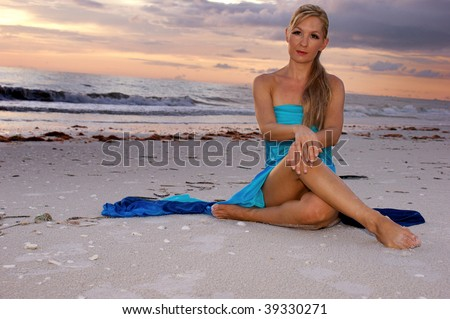 woman sitting cross legged on beach looking directly at the viewer, her legs are crossed and her hands are resting on her knees. with copy space. - stock photo