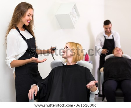 Woman sitting in a black peignoir in a hair beauty shop near sink waiting for a hairdresser to wash her hair
