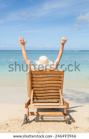 woman sitting in a canvas chair on the beach raising her arms ind the air, concept for happy holidays or vacation, Flic en Flac, Mautitius, Africa - stock photo