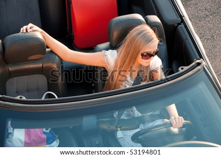 Woman sitting in a car, with her baggage - stock photo